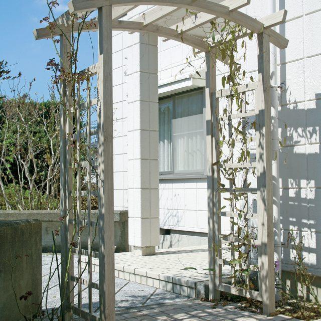 白い建物と調和した木目柄のアルミ製パーゴラ