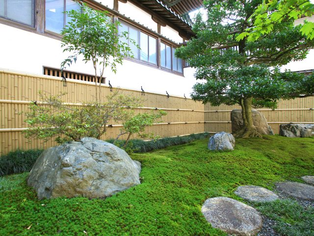 庭石がバランスよく配置された美しい和風庭園の背景に