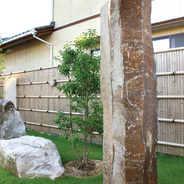 古竹ボードを貼った塀。点在する庭石と相まって、枯れた味わいのある庭に