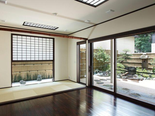 大開口の窓から見える庭と、和モダンの雪見窓から見える庭。一連の竹垣が異なる表情を見せる