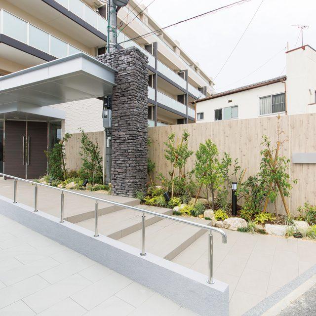 集合住宅の玄関へのアプローチにエバーアートボードフェンス6型を採用