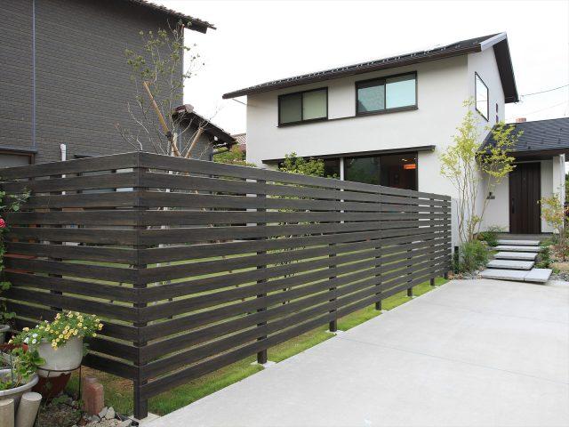芝生の緑とのコントラストが美しい木目調フェンス