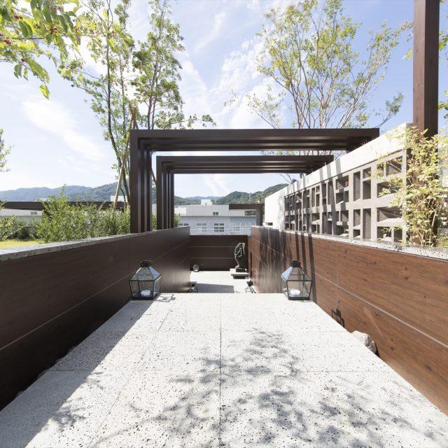 モダンな木目柄を壁一面にあしらったリゾート感のあるアプローチ