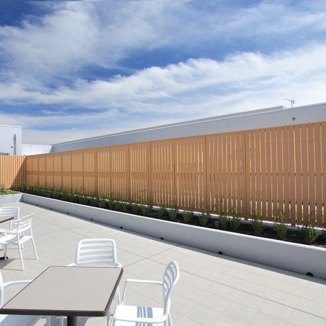 屋上の癒やしのスペースを木目調のフェンスでやさしい印象に