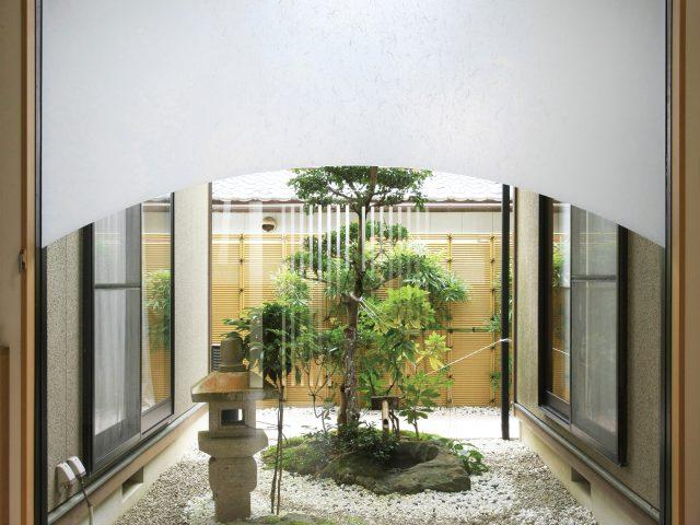 隣地境界と坪庭の背景を兼ねて。上部にすき間を作ることで、圧迫感をおさえられる