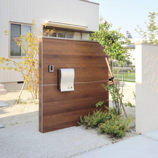 板状の木目柄の門袖と、エバーアートウッドのフェンスを組み込んだ白い塀をバランスよく配置