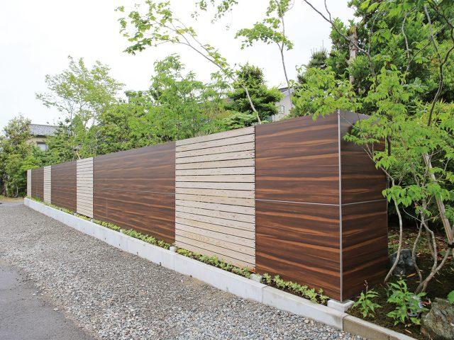 木目柄のオーガンウッドダークで背景の緑と調和するフェンスに