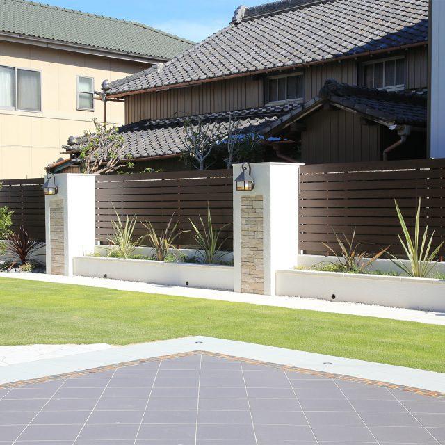 木目調のやさしい色合いのフェンスで植え込みの背景に