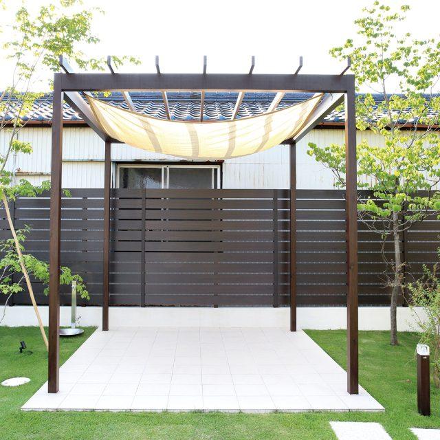 パーゴラポーチと組み合わせて。広い敷地を囲うフェンスも、モクプラボードなら手軽に施工できる