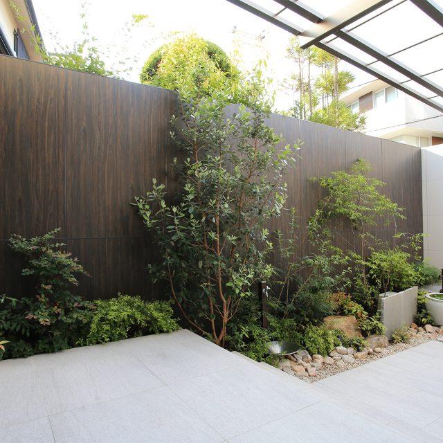 植栽の緑が引き立つ木目調の境界塀
