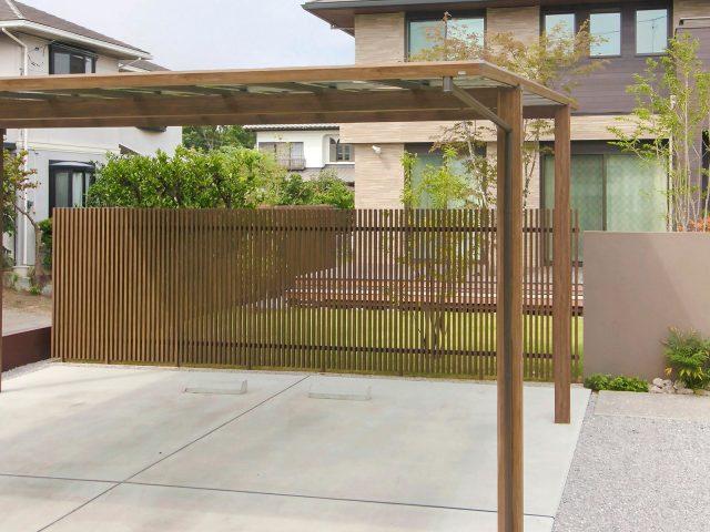 駐車スペースと庭の境界用フェンスに千本格子足付ユニット。木目柄でやさしい印象に