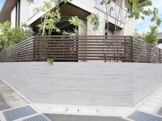 上部に風通しのよいフェンスをのせ、RC杉板目調タイルのセラ ウォールで敷地を囲んで