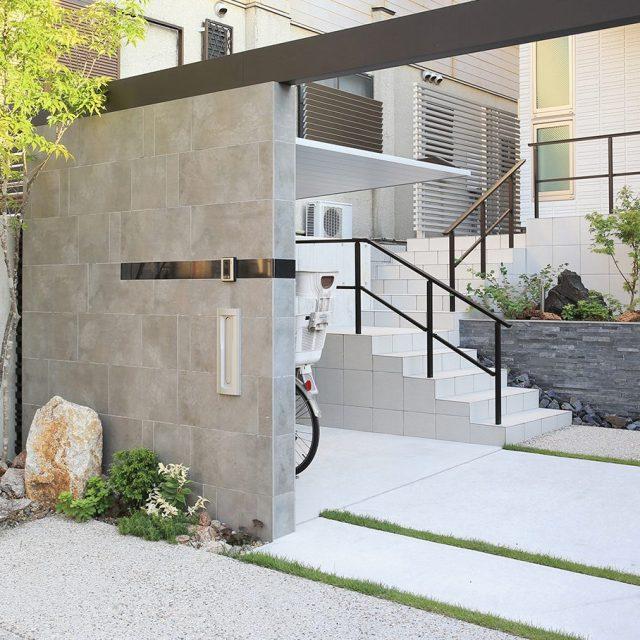 タイルを乱貼りして門壁の意匠に。打放しコンクリートの塀と相性よく