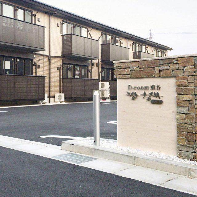ブロックと木目柄のエバーアードボードを使って集合住宅のサインに