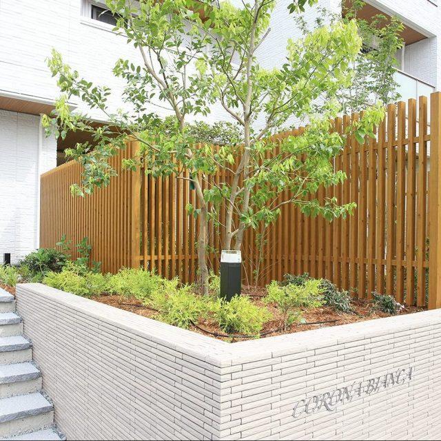 木目調のアルミ製格子フェンス。リバーシブル仕様で表裏もすっきり、植栽の緑ともよく調和します
