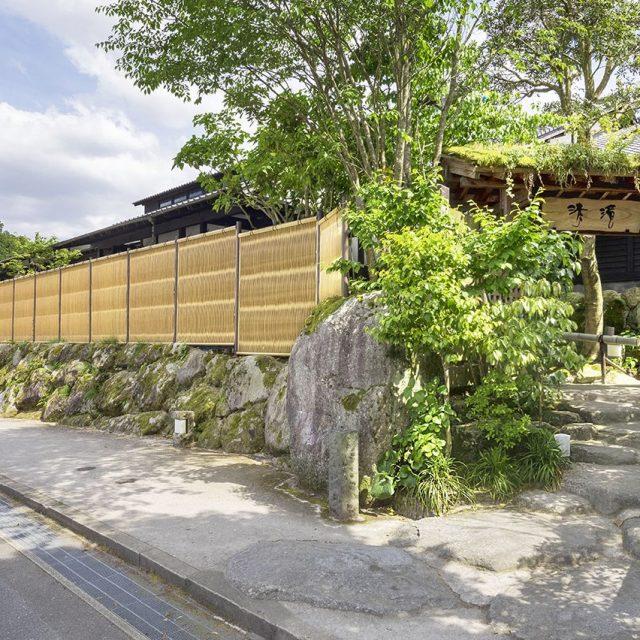 歴史を感じる石積みの塀や、庭石を配置した門まわりと調和する大津垣フェンス