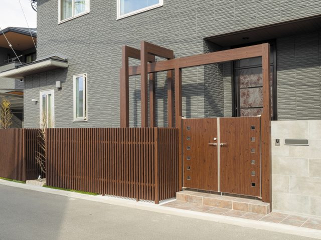 木目調カラーで統一した立体的な門まわりと、駐車スペース奥にはくつろぎの空間を設けました