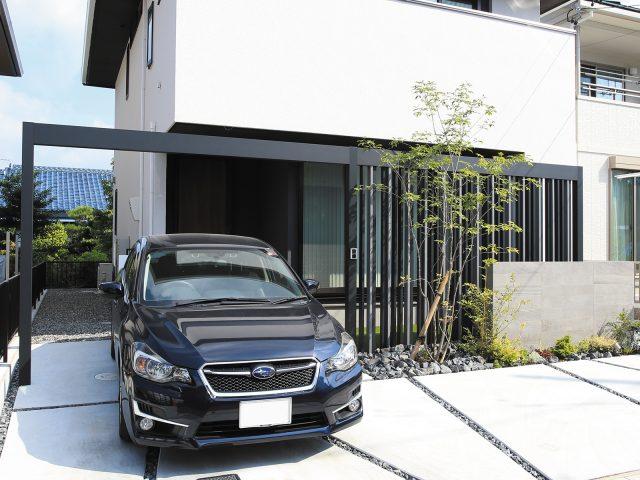 黒いホームヤードルーフと格子材を組み合わせた門まわり。白い建物とも調和します