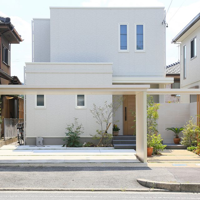 建物に合わせた白い木目調の車庫まわり。植栽とも調和して明るい印象に