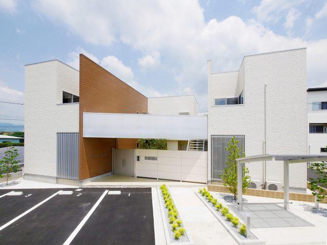 ホワイトパイン柄のエバーアートボードを使い、エントランスゲートの壁面に。白い木目が建物と調和します
