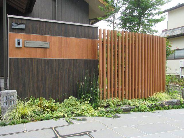 木目調のアートボードと、格子材で門まわりをやさしい印象に