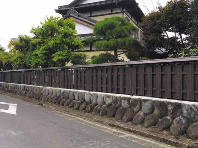 木目柄のこだわり板を使って大和塀をつくる。垣根用小屋根を付けて和風建築とも調和します