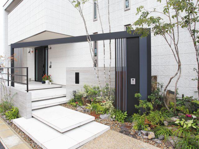 白を基調とした建物の門まわりにワイドなフレームで立体的なアクセントに