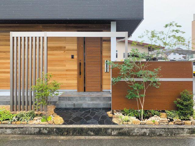 ステンカラーのフレームと木目調の門袖を組み合わせて。植栽の緑とも調和します
