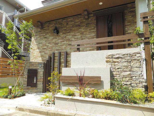 天然石貼りの門袖に、エバーアートウッド こだわり板、格子材を組み合わせて上質な印象に
