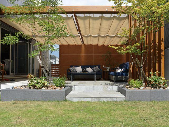 ホームヤードルーフによる室内のリビングから繋がるガーデンテラス。木目調カラーでまわりの植栽とも調和します
