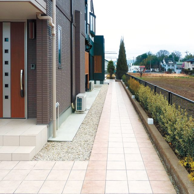 建物のアプローチに淡いカラーのタイル2色を使ってやさしい印象に