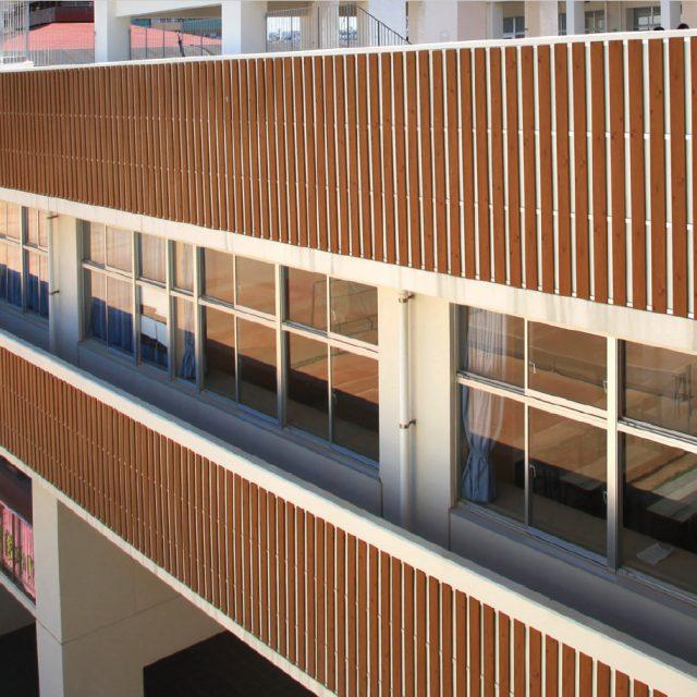 ウッドテイストの壁面材で、人の多く集まる学校施設のデザイン性を向上