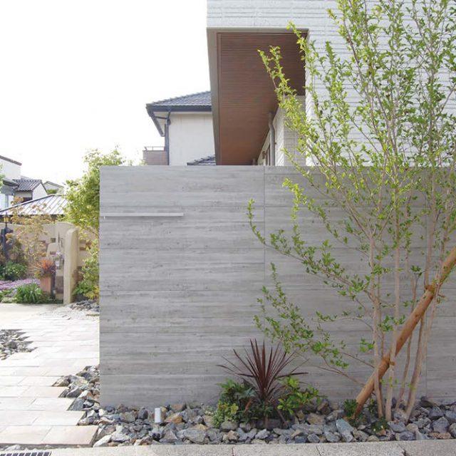 白い外壁とセラウォールを背景に植栽の緑とのコントラストが美しい