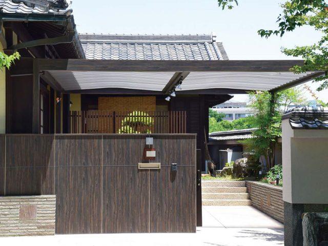 駐輪場の屋根に門壁と同系色のブラックエボニー色を使った「ホームヤードルーフ カーヤードスタイル」で趣のあるエントランス空間に