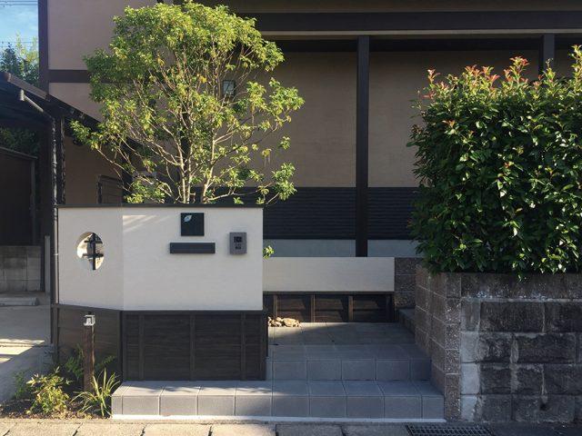 人工の黒竹を組んだ丸窓が個性的。モダン和風の建物と調和した門まわりに